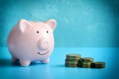 Piggy bank on a blue background. Three stacks of coins are reduced in order. The symbol is the accumulation and. Conservation of money. A vivid photo with a Royalty Free Stock Photo