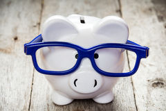 Piggy bank with blue glasses. On old wooden floor Royalty Free Stock Photography
