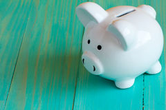Piggy bank on the blue wooden surface Royalty Free Stock Images
