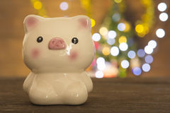 Piggy bank with bokeh Christmas tree Royalty Free Stock Photo