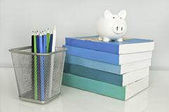 Piggy bank, books, blue and green pencils Royalty Free Stock Photography