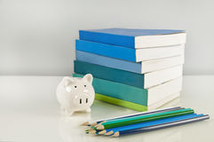 Piggy bank, books, blue and green pencils Royalty Free Stock Image
