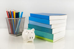 Piggy bank, books and colorful pencils Royalty Free Stock Image