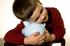 Piggy bank boy. Boy holding on to a piggy bank Royalty Free Stock Photos
