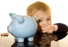 Piggy bank boy hiding. Toddler hiding behind a blue piggy bank Royalty Free Stock Photo