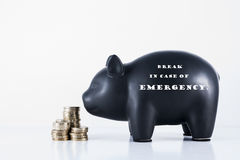 Piggy Bank Break in case of Emergency. Black piggy bank and some coins with the motif - Break in case of Emergency Stock Photo