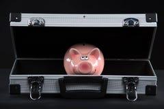 Piggy bank in briefcase studio cutout. Piggy bank on dark background stock photo