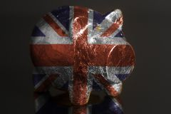 Piggy bank with British flag. On a black background stock images