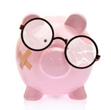 Piggy bank with broken eyeglasses Royalty Free Stock Photo