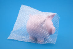 Piggy bank in bubble wrap on blue background
