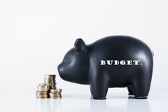 Piggy Bank Budget. Black piggy bank and some coins with the motif - Budget Stock Photo
