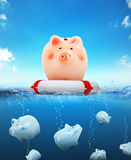 Piggy bank with buoy floating on water Royalty Free Stock Image