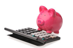 Piggy bank on calculator. Isolated on white Stock Photo