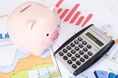 Piggy bank and calculator with  business charts Royalty Free Stock Photos