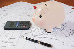 Piggy bank with calculator and business reports Stock Photo