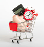 Piggy bank, calculator and clock in shopping cart Stock Image