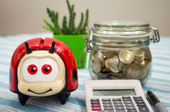 Piggy bank, calculator and coin filled glass jar. Piggy bank, calculator, pen and coins filled glass jar on the table Royalty Free Stock Photo