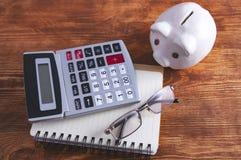 Piggy bank calculator documents stock image