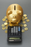Piggy bank with calculator. Golden piggy bank with calculator royalty free stock image