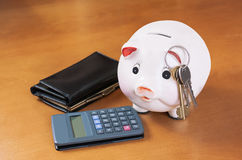 Piggy Bank, calculator, keys  and purse on wood table Stock Images