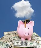 Piggy bank cash with graduation cap and blue sky. Piggy bank with graduation cap, on cash with blue sky Royalty Free Stock Images