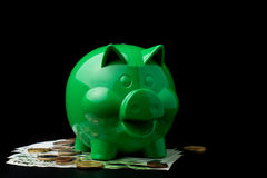 Piggy bank. Caucasian hand putting coin in piggy bank on black background Stock Photos