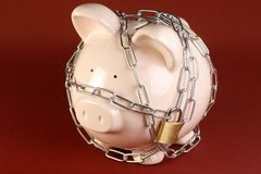 Piggy bank in chains. Security concept pink piggy bank wrapped in chains and padlocked Stock Images