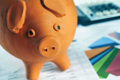 Piggy bank, charts and calculator. Closeup of a piggy bank on a desk with bills and charts and a calculator in the background Royalty Free Stock Photos