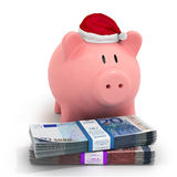Piggy bank in a Christmas hat with bundles Stock Photos