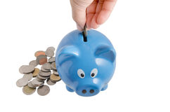 Piggy bank. Coil drop on blue piggy bank Stock Photography