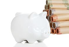 Piggy bank with coin rolls Stock Photo