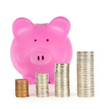 Piggy bank with coin stacks. Stacks of coins in front of pink piggy bank showing growth Royalty Free Stock Image