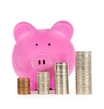 Piggy bank with coin stacks. Stacks of coins in front of pink piggy bank showing growth Royalty Free Stock Photos