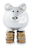 Piggy bank on coin stacks. Silver piggy bank balancing on stacks of silver coins, isolated on white background stock photos