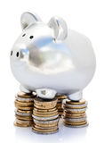 Piggy bank on coins. Silver piggy bank balanced on piles of coins with white background royalty free stock photo