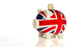 Piggy bank with coins. Piggy bank in the colors of the British union jack Royalty Free Stock Image