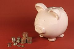Piggy bank and coins. Traditional pink piggy bank with a stack of coins on a red background Royalty Free Stock Image