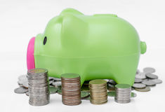 Piggy bank on coins background and arranged in stack Royalty Free Stock Photos