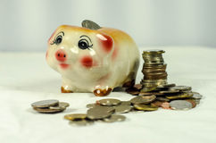 Piggy bank with coins on background Royalty Free Stock Photo