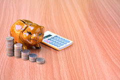 Piggy bank, coins and calculator out on wood table Royalty Free Stock Images