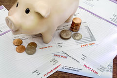 Piggy Bank with coins and delinquent bills. Piggy bank with coins and household bills indicating hardship royalty free stock images