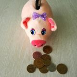 Piggy bank and coins of different countries stock photography