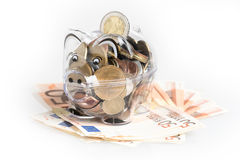 Piggy bank, coins and euro bills. Money saving concept. Banknotes closeup. Isolated background Royalty Free Stock Images