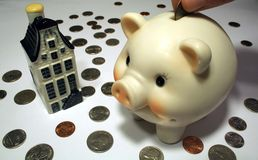 Piggy Bank, Coins, and Model Home. This is an image of a piggy bank with coins and a model home, depicting the American Dream stock photo