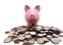 Piggy bank on coins. Piggy bank on a pile of coins Royalty Free Stock Photo