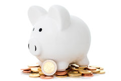 Piggy bank and coins pile Royalty Free Stock Photography