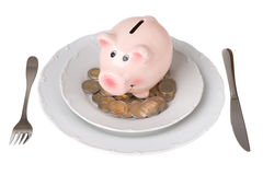 Piggy bank with coins on a plate Royalty Free Stock Image