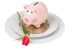 Piggy bank with coins on a plate Stock Photo