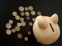 Piggy bank with coins. Save money concept on the black background Stock Photos