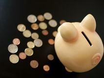 Piggy bank with coins. Save money concept on the black background Royalty Free Stock Photos